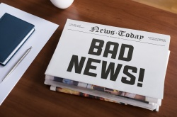 "Newspaper concept with hot topic ""Bad news"" lying on office desk."